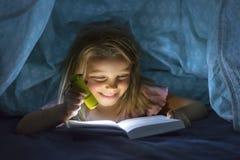 在床罩阅读书下的美好的美好和相当小的白肤金发的女孩6到8岁在黑暗在与火炬光的晚上 库存照片