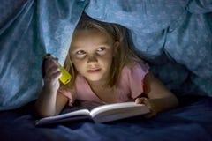 在床罩阅读书下的美好的美好和相当小的白肤金发的女孩6到8岁在黑暗在与火炬光的晚上 图库摄影