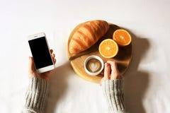 在床舱内甲板位置的早餐 妇女在床上递拿着咖啡和电话,木裁减用新鲜的新月形面包和草莓 顶层 库存图片
