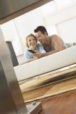 在床观看的电视上的年轻夫妇 免版税图库摄影