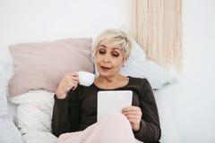 在床饮用的早晨咖啡的一名年长妇女使用一种片剂观看新闻或与社交的朋友聊天 免版税图库摄影