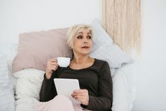 在床饮用的早晨咖啡的一名年长妇女使用一种片剂观看新闻或与社交的朋友聊天 库存照片