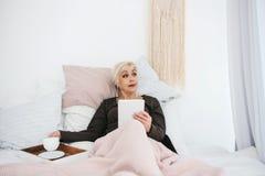 在床饮用的早晨咖啡的一名年长妇女使用一种片剂观看新闻或与社交的朋友聊天 图库摄影