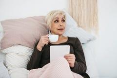 在床饮用的早晨咖啡的一名年长妇女使用一种片剂观看新闻或与社交的朋友聊天 免版税库存图片