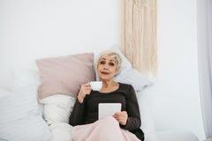 在床饮用的早晨咖啡的一名年长妇女使用一种片剂观看新闻或与社交的朋友聊天 库存图片