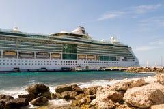 在库拉索岛靠码头的游轮由岩石防波堤 库存照片
