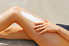 在应用在腿的女性手上的特写镜头遮阳纸奶油 库存照片