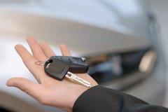 在店员的汽车钥匙张开手 免版税库存图片