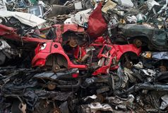 在废品旧货栈的被废弃的红色汽车 库存图片