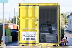 在废物转储跳的老电视电视显示器个人计算机屏幕回收在黄色容器的被堆积的堆帮助环境关于 免版税库存图片