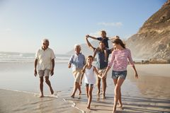 在度假一起走沿海滩的多一代家庭 图库摄影