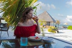 在度假在一个热带海岛吃一顿健康早餐的年轻女人 免版税库存图片