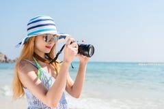 在度假拍摄与在海滩的一台照相机的愉快的亚裔妇女与天际在背景中 库存图片