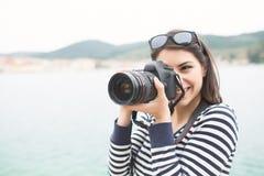 在度假拍摄与在海滩和微笑的一台dslr照相机的愉快的妇女 免版税图库摄影