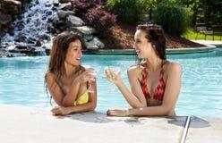 在度假的女朋友在游泳池 免版税库存照片