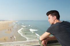 在度假的英俊的年轻人在海滩 免版税库存图片