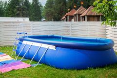 在庭院中的蓝色可膨胀的水池 免版税库存图片