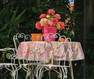 在庭院中间的老桌有桃红色花的 免版税库存照片