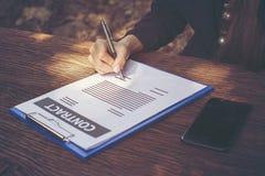 在庭院书桌上的女商人签署的合同文件 图库摄影