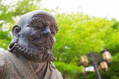 在庭院寺庙的修士雕象 图库摄影