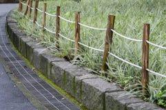 在庭院旁边的绳索和木头篱芭 免版税库存照片