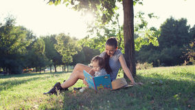 在庭院的时髦的母亲和小孩阅读书在夏天乐趣期间 免版税图库摄影
