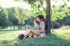 在庭院的时髦的母亲和小孩阅读书在夏天乐趣期间 图库摄影