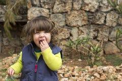在庭院里吃果子的小孩女孩 库存照片