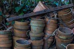 在庭院里堆积的老肮脏的花盆 免版税库存图片