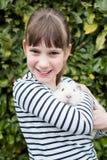 在庭院里照看宠物试验品的女孩画象  库存图片