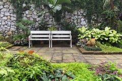 在庭院里面的两条白色长凳 免版税库存图片