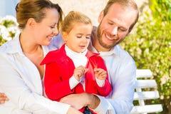 在庭院长凳的家庭在家前面 免版税库存照片