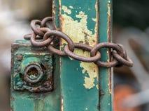 在庭院门附近被包裹的老生锈的铁链子 库存图片