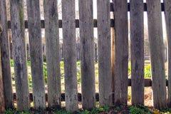 在庭院附近的老,土气尖桩篱栅 免版税库存照片