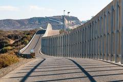 在延伸到遥远的小山的圣地亚哥和提华纳之间的国境墙壁 免版税库存照片