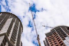 在建筑两个房子或摩天大楼和与云彩的蓝天的背景的一台建筑用起重机 库存图片