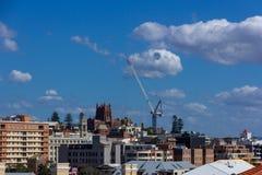 在建筑大厦的塔吊在有蓝色s的城市 图库摄影
