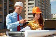 在建筑工地前面的二个建筑师工作 库存照片