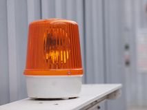 在建筑边的橙色警报器光在安全标志 免版税库存照片