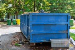 在建筑附近的被装载的大型垃圾桶 免版税库存照片