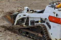 在建造场所滑行装载者的小挖掘机美洲野猫在建造场所 库存照片