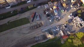 在建造场所的一种黄色挖掘机装载水泥和被击碎的石头入桶并且去除他们对在站点的起动工作 股票录像