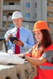 在建造场所的二个建造者工作 免版税库存照片
