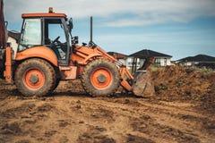 在建造场所的工业机械 反向铲装载者工作 免版税图库摄影