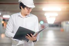 在建造场所的年轻亚洲工程师待办卷宗 库存图片