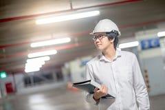 在建造场所的年轻亚洲工程师待办卷宗 免版税图库摄影
