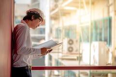 在建造场所的年轻亚洲工程师待办卷宗 免版税库存照片