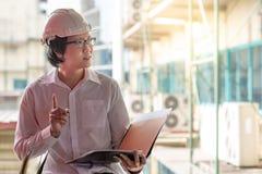 在建造场所的年轻亚洲工程师待办卷宗 库存照片