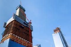 在建造场所的建筑用起重机在纽约修建办公室摩天大楼大厦在日落时间 免版税库存图片