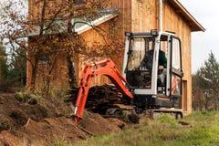 在建造场所的微型挖掘机 一个家庭房子的建筑在森林附近的 免版税图库摄影